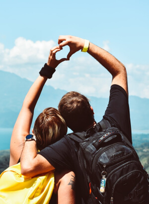 couple on mountain holding hands up as heart