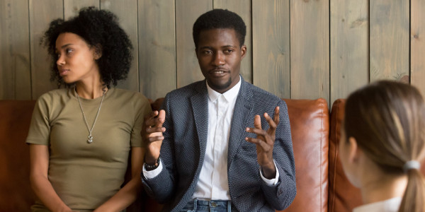why marriage counseling fails -African man talking to family counselor, frustrated husband sharing marital problems while offended wife sitting silent on couch, black unhappy couple visiting psychologist, marriage counseling