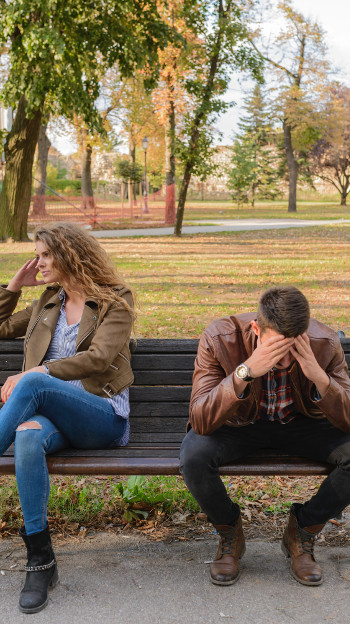 man woman sitting on bench, frustrated
